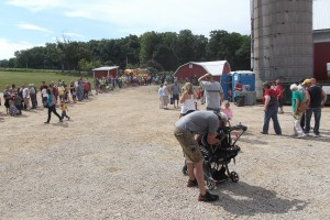 The line of people waiting to eat wound around the farm yard.
